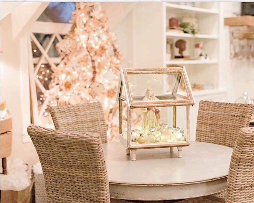 small vintage greenhouse with a white Santa inside and filled with silver vintage Christmas ornaments is the table centerpiece for my round dining room table with 4 woven chairs around it and the white vintage Christmas tree in the background