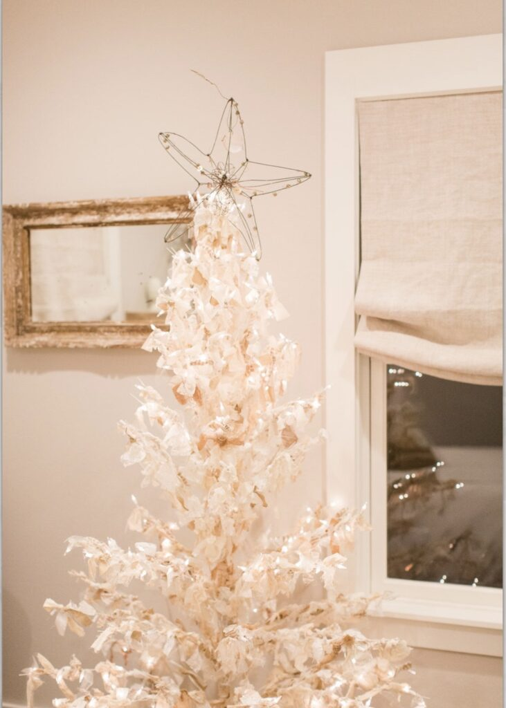 """white wire Christmas tree with lights and tied with fabric strips to create a """"rag tree"""".  A wire star is the tree topper"""