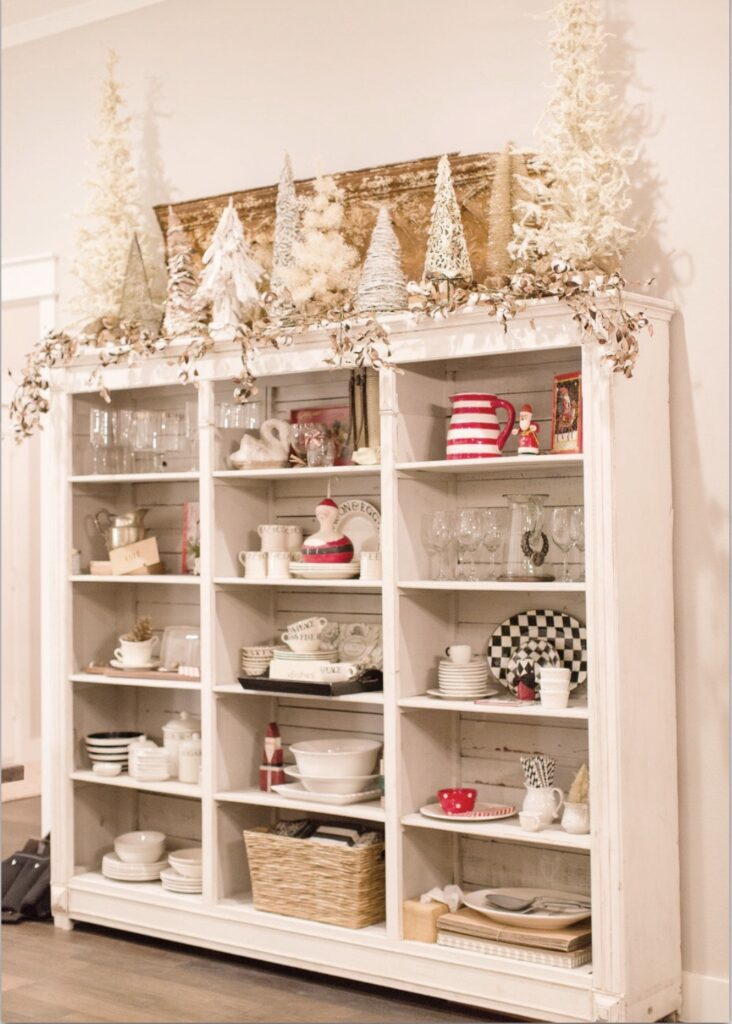 Large white vintage kitchen open hutch filled with white ironstone dishes, Mackenzie Childs serving pieces and touches of red Christmas decor.  The top of hutch is a collection of my larger white Christmas trees in my collection.