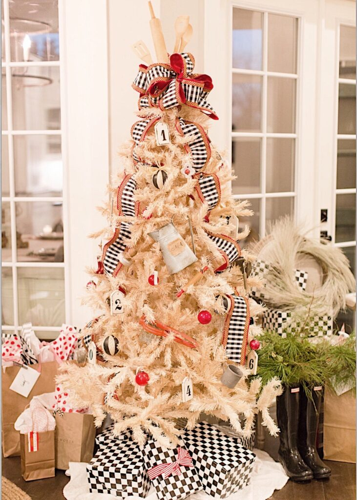 A white vintage Christmas tree decorated with red and black accents.  Black and White Check ribbon with red border (Mackenzie Childs inspired), vintage mini kitchen utensils, vintage red christmas balls, white wooden tags with black numbers, black and white striped Christmas balls adorn the tree.  A wooden rolling pin, and serveral wooden utensils are sticking out of the top of the tree for a tree topper and a bow tied from the black check ribbon is at the base.  Packages with black check wrapping paper are beneath the tree and my black Hunter rain boots stand beside the tree with greenery tucked inside