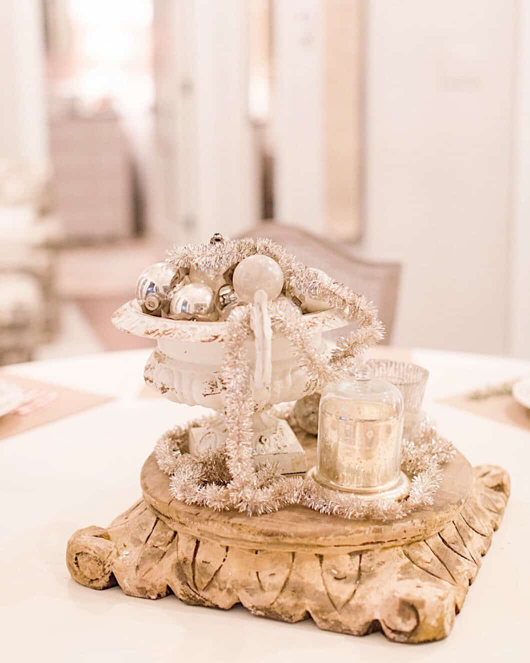 bowl of silver vintage Christmas balls in a vintage urn on a vintage pedestal centered on my large white dining round dining table for a Christmas in July Home Tour table centerpiece