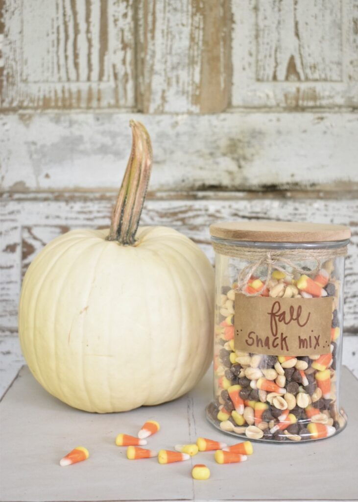 fall snack mix with candy corn, peanuts and chocolate chips in a glass jar with a wooden lid sitting beside a white pumpkin