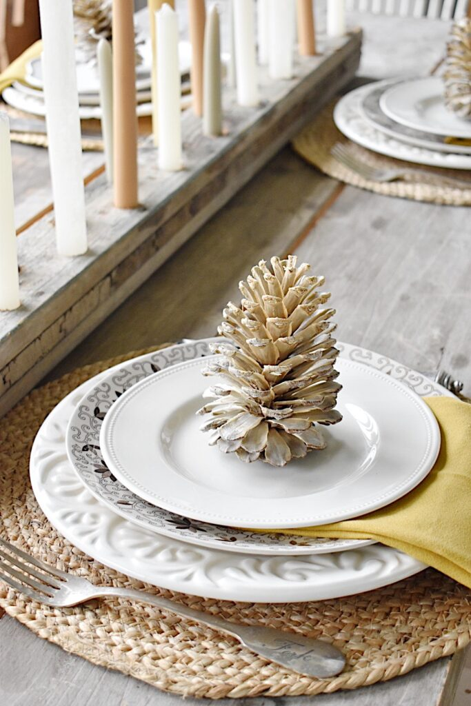 fall tablesetting with bleached pinecone in center of stack of white plates and brown transferware plates and gold napkin between plates