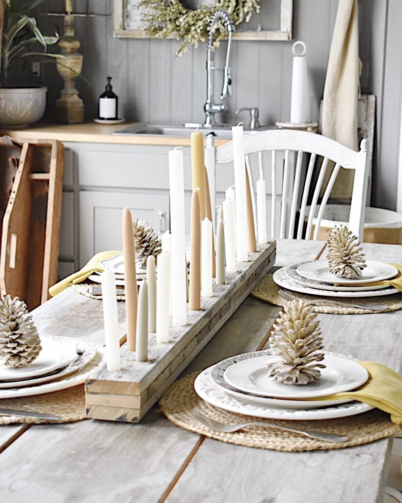 long narrow candleholder out of rustic wood with tan and gray tapers down the center of dining table with place settings of white dishes mustard color napkin on a round jute placemat with a bleached pinecone on top of each plate