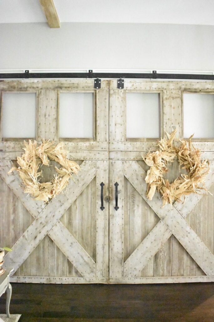 large cornhusk wreaths hanging on 2 large barn doors inside my living room