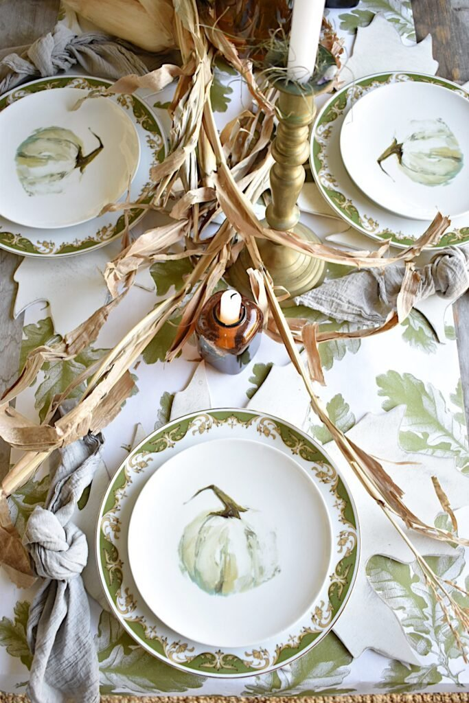 thanksgiving tablescape with cornstalks down center of table white plates with white pumpkins plaid napkin tied in knot beside plates