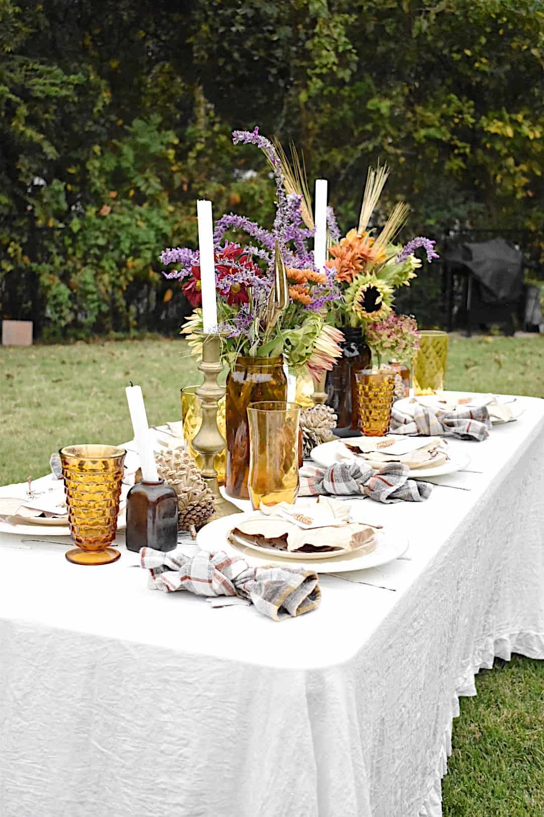 fall tablescape with amber glasses, plaid napkins tied in a knot, white dinner plates, dried leaves on top of plates and fall florals in a large amber vase in center of table