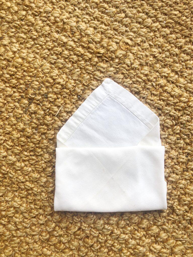 napkin folding into an envelope shape