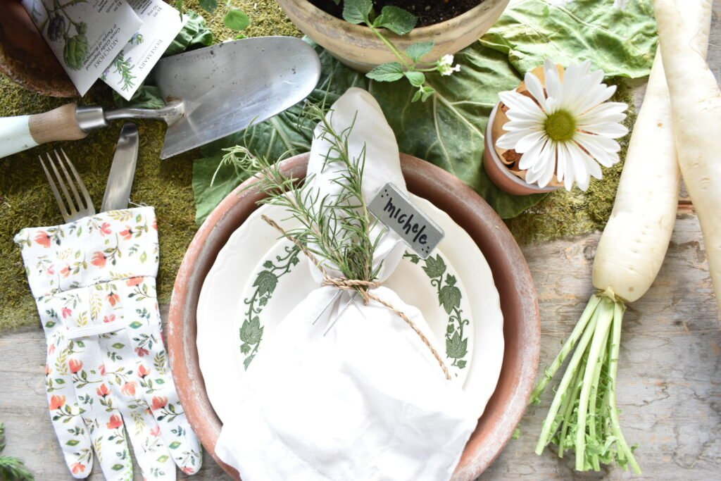 a garden inspired place setting.  A large terra cotta plant tray is used as a charger.  A large white dinner plate topped with a ivy border salad plate is at each place setting.  A garden glove is used to hold silverware to the left of the plate.  A white linen napkin tied with jute and a sprig of fresh rosemary tops each plate