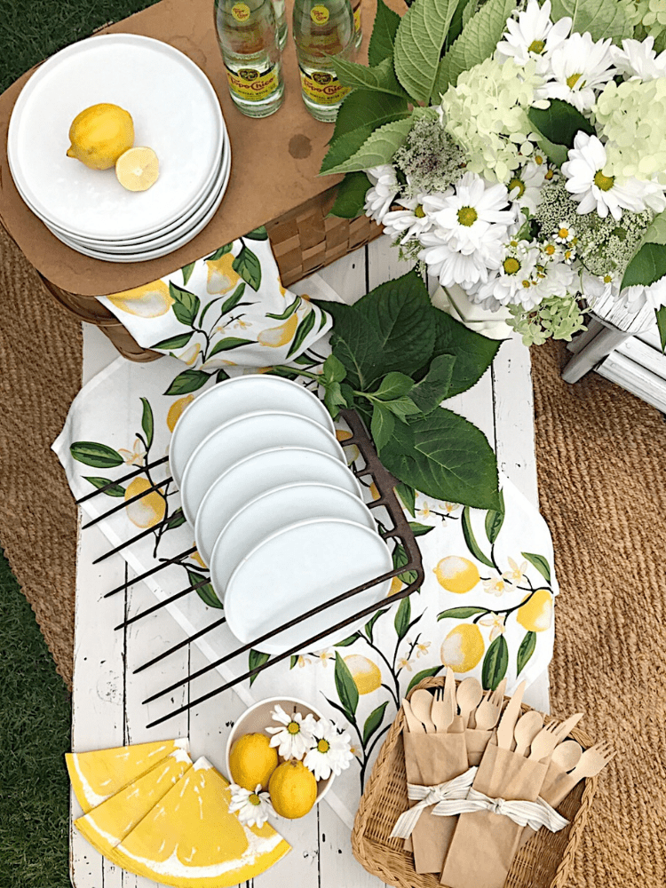 aerial view of a summer picnic tablescape.  A white table with white plates, white flowers in a vintage white vase, bamboo utensils, lemon print napkins, and 4 bottles of Topo Chico