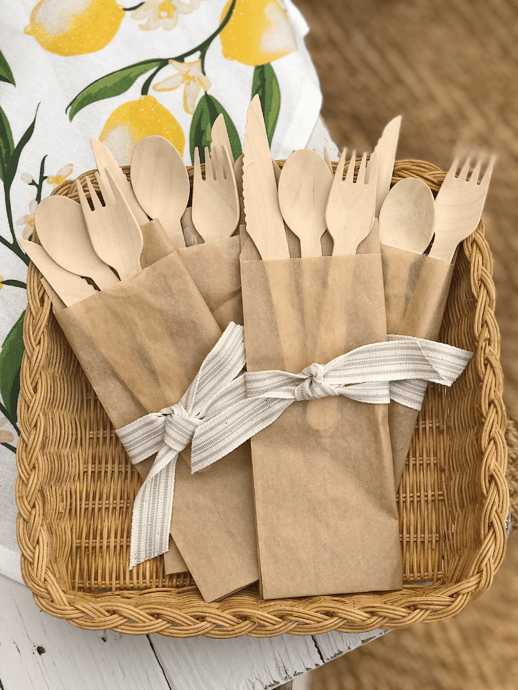 bamboo utensils served inside brown sandwich bags and tied with a ribbon