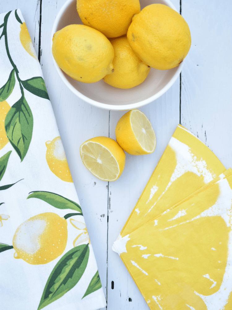 lemon print dishtowel, lemon wedge paper napkins and a bowl full of lemons