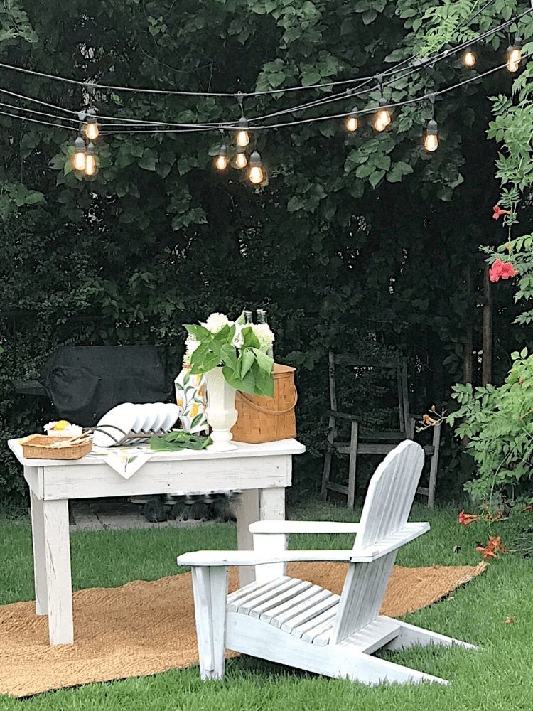 outdoor summer picnic set up, with sting light overhead and a white adirondack chair beside table.  A vintage picnic baskets sits on the table along with white plates, white flowers in a white vintage flower vase, 4 bottles of Topo Chico and bamboo utensils and lemon print napkins