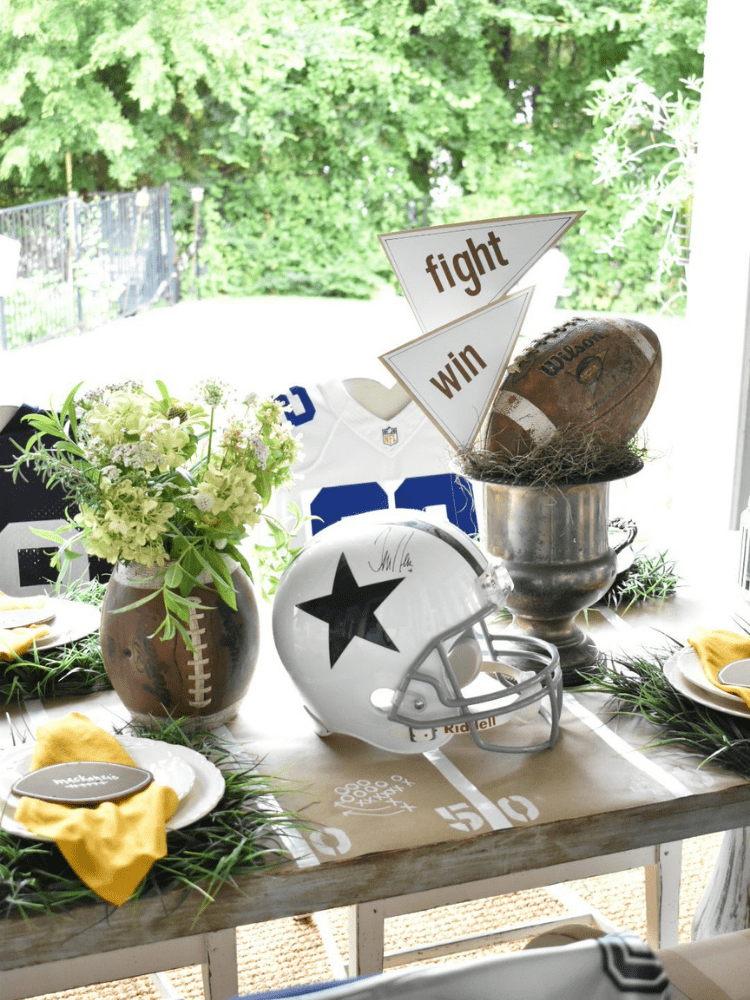 football themed centerpiece, a football with the ends cut off to use as a vase and filled with white flowers , a silver wine bucket used as a trophy and holds green moss and a football and pennants made from scrapbook paper, and a football helmet