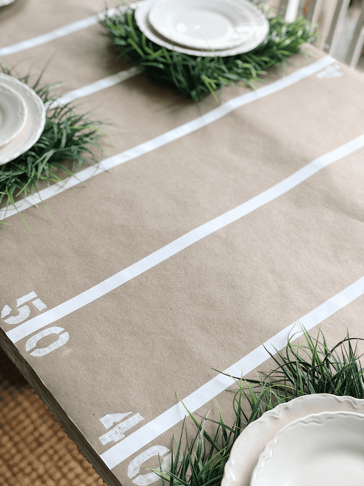 brown paper table runner with yard lines created from white tape and stenciled numbers at each yard line
