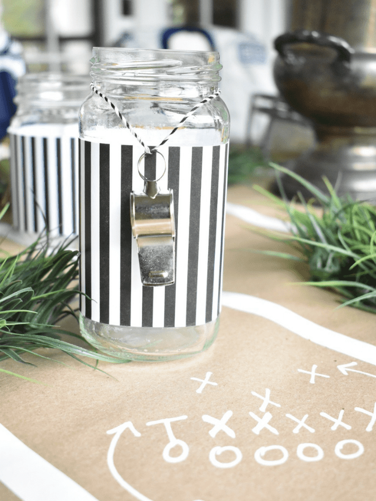mason jar wrapped with a strip of narrow black and white striped paper and a whistle on a string around neck of glass to resemble a referee