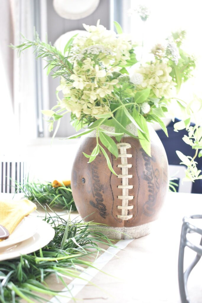 vase made from an old football filled with white flowers