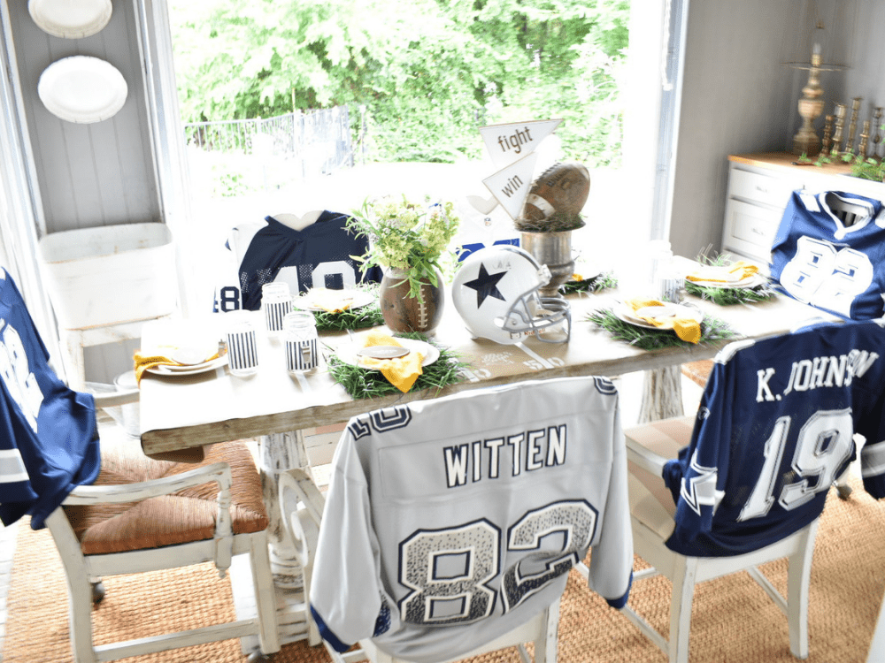 """overall view of football tailgate tablescape.  football jerseys over the back of chairs for slipcovers, football helmet and silver wine bucket """"trophy"""" for centerpiece"""