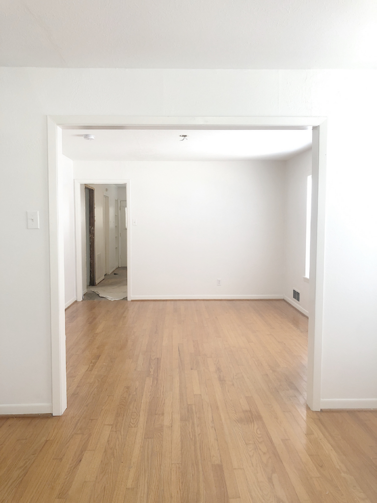 unfurnished dining room of a small cottage with white walls and light hardwood floors