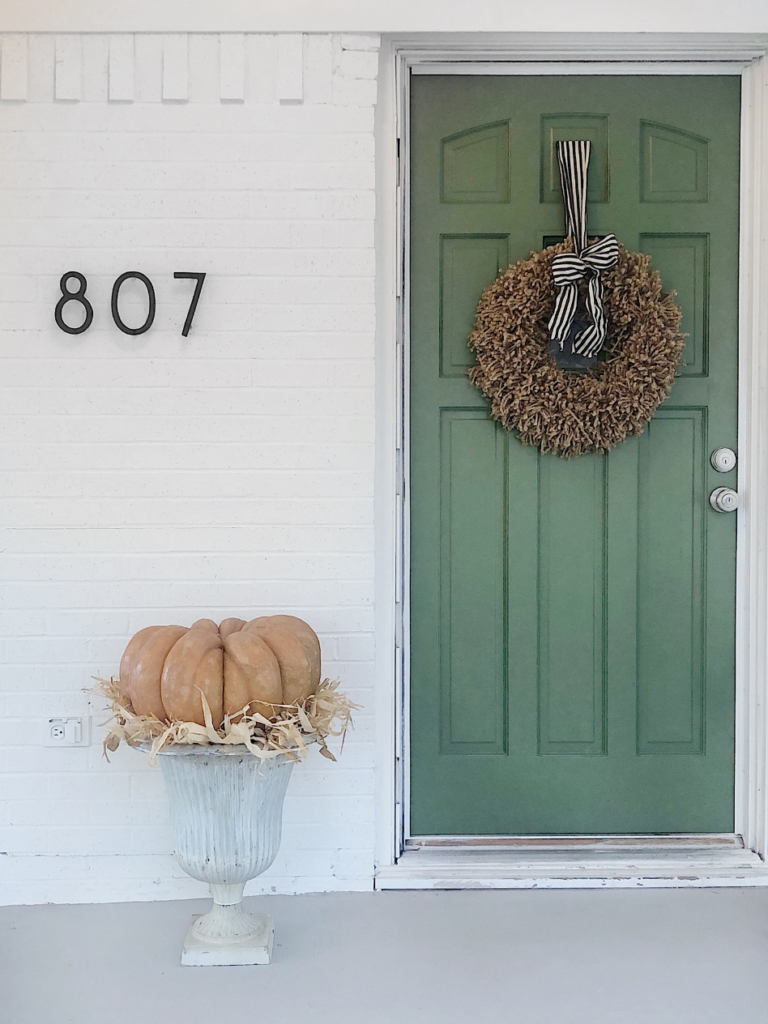 green door with jute wreath with black and white bow white metal urn with a huge peach color cinderalla pumpkin on top of urn