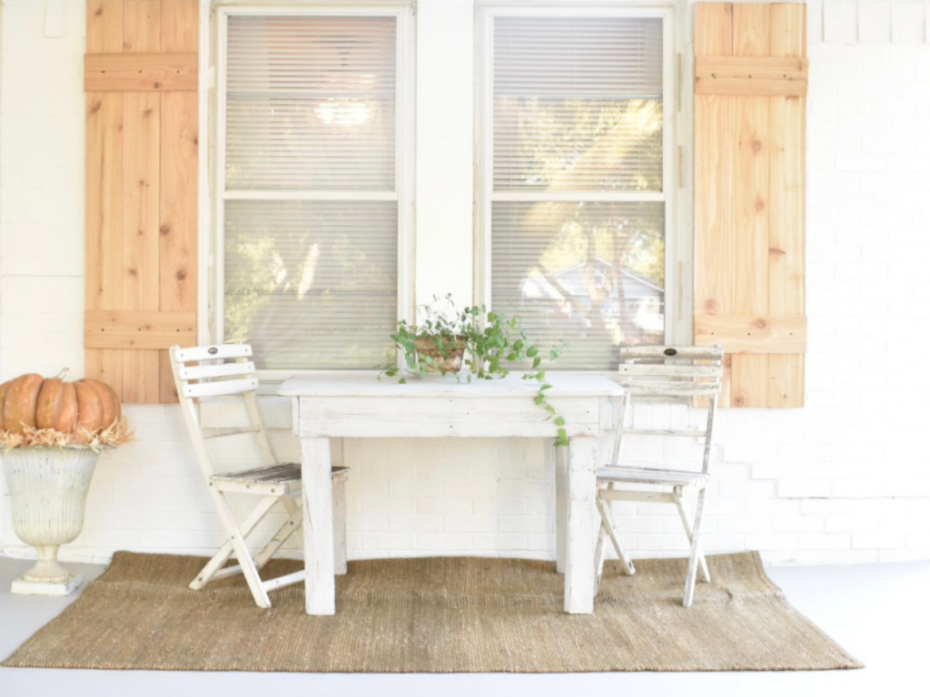 front porch of white house with cedar shutters on the window white table and 2 white chairs at table and a sisal rug underneath table plant on table