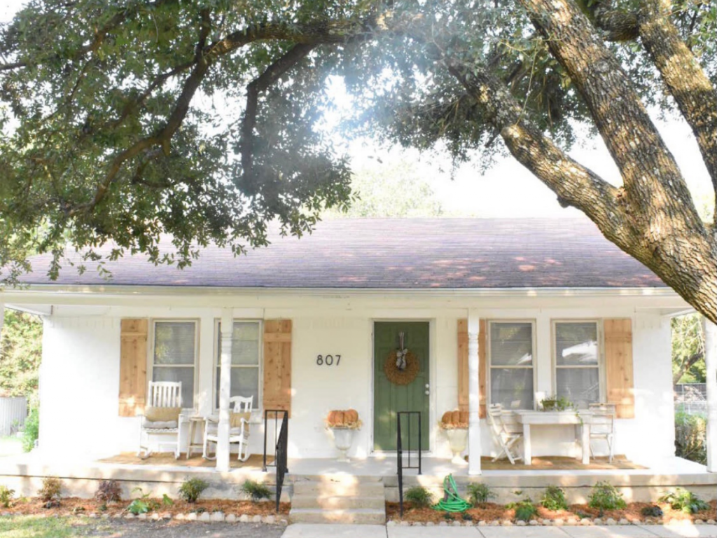 exterior of front of white painted brick cottage with green front door with jute wreath 2 white rockers white table and 2 white chairs 2 white urns with large pumpkins on top