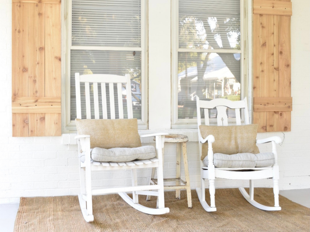 2 white rockers on front porch of white painted brick house with cedar shutters