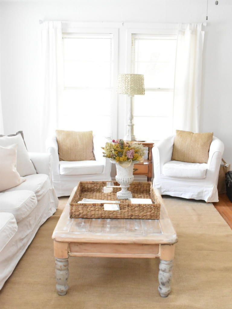 living room with 2 white slipcovered chairs white slipcovered sofa light wood coffee table light tan rug large wicker basket on coffee table with urn of flowers