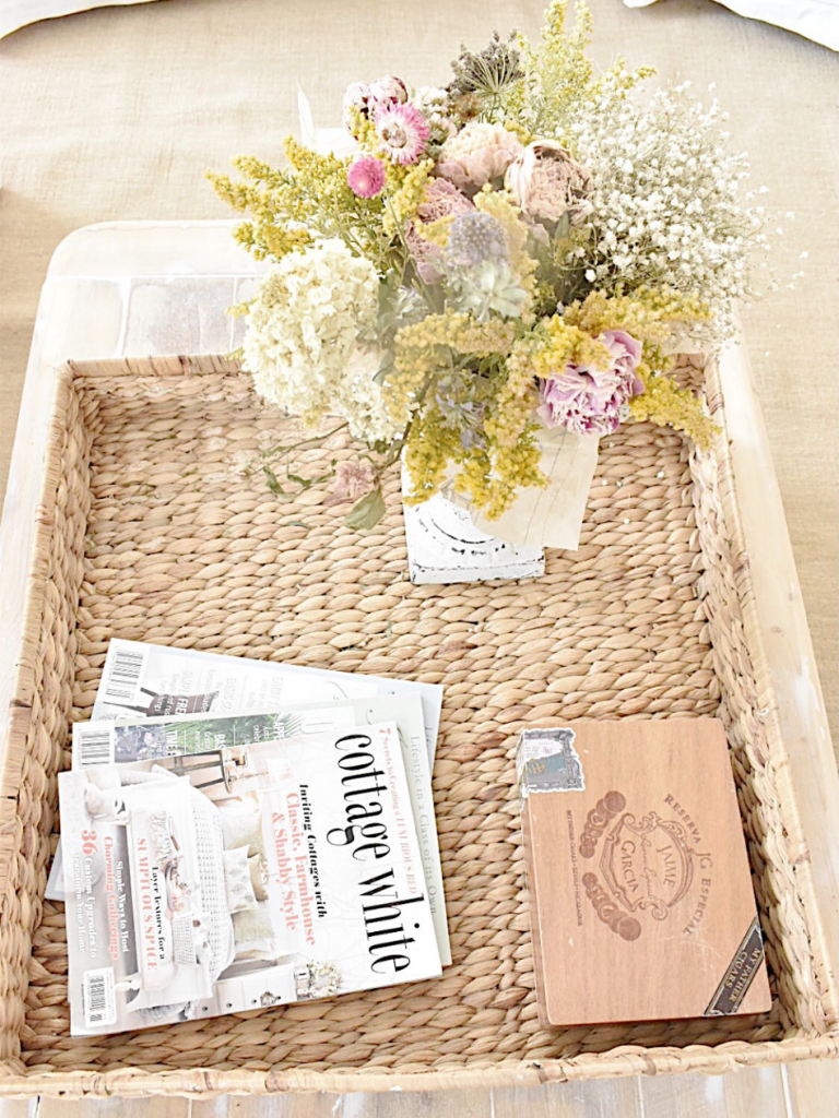 large square woven basket on top of coffee table with cigar box magazines white urn with dried flowers