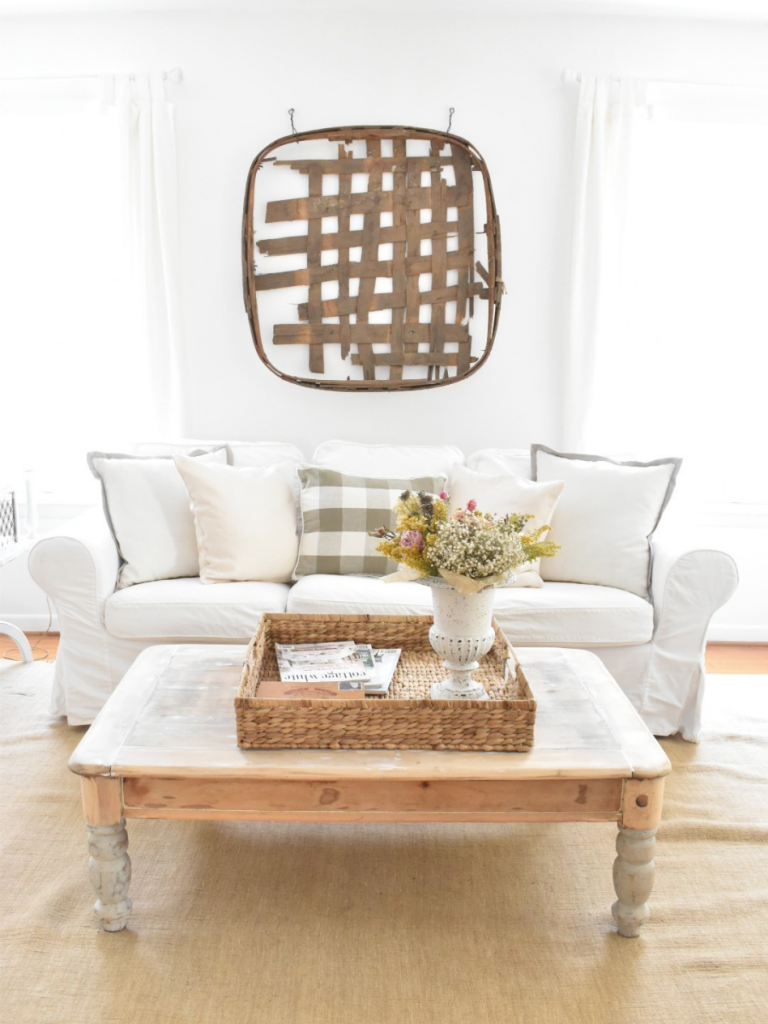white slipcovered sofa with vintage tobacco basket on wall white curtain panels light wood coffee table large square woven basket on coffee table with magazines and a white urn with dried flowers light tan area rug