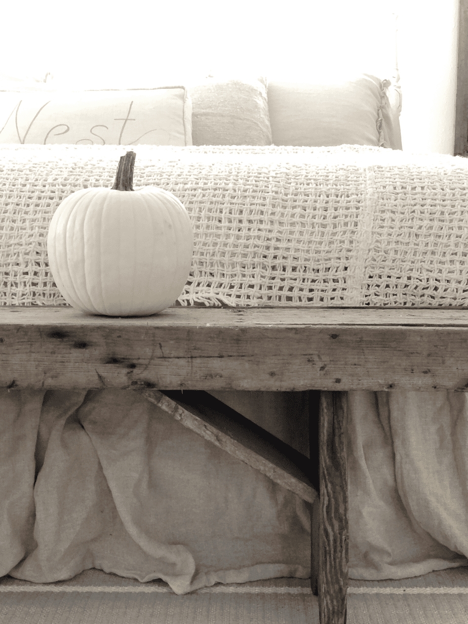 white pumpkin sitting on rustic bench with end of bed showing behind it with woven cream throw across end of bed