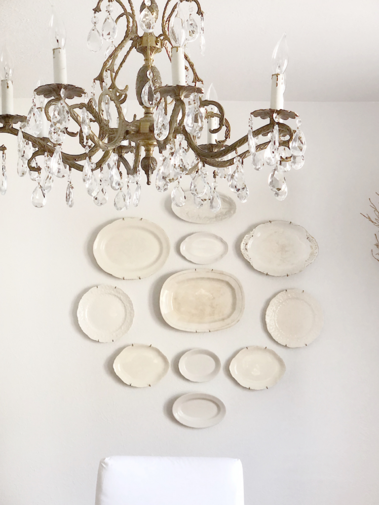 a collection of white ironstone plates hanging on the wall