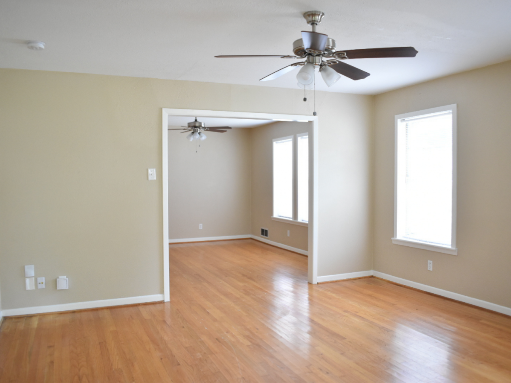 living room with tan wall white trim ceiling fan light hardwood floors no furniture