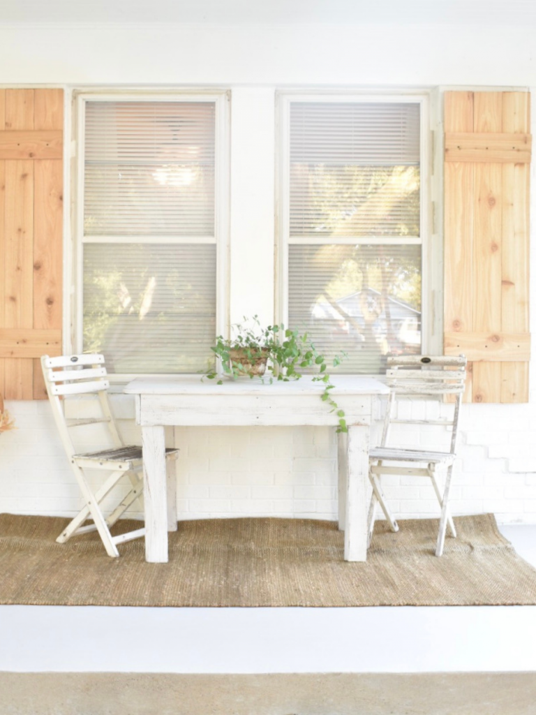 front porch of white painted brick house white table with a small white chair on either side on jute rug plant on table cedar shutters behind