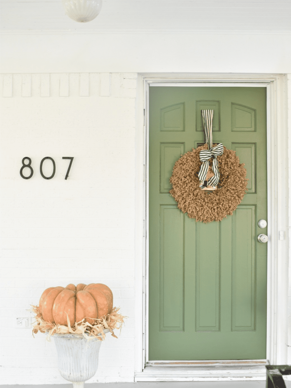 front of white cottage with green door white metal urn with large pumpkin on top of urn jute wreath hanging on door