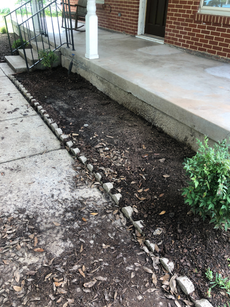 empty flower beds in front of house