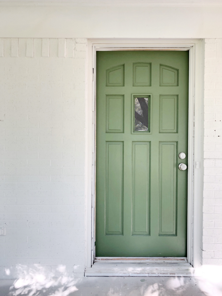 green front door on white brick house