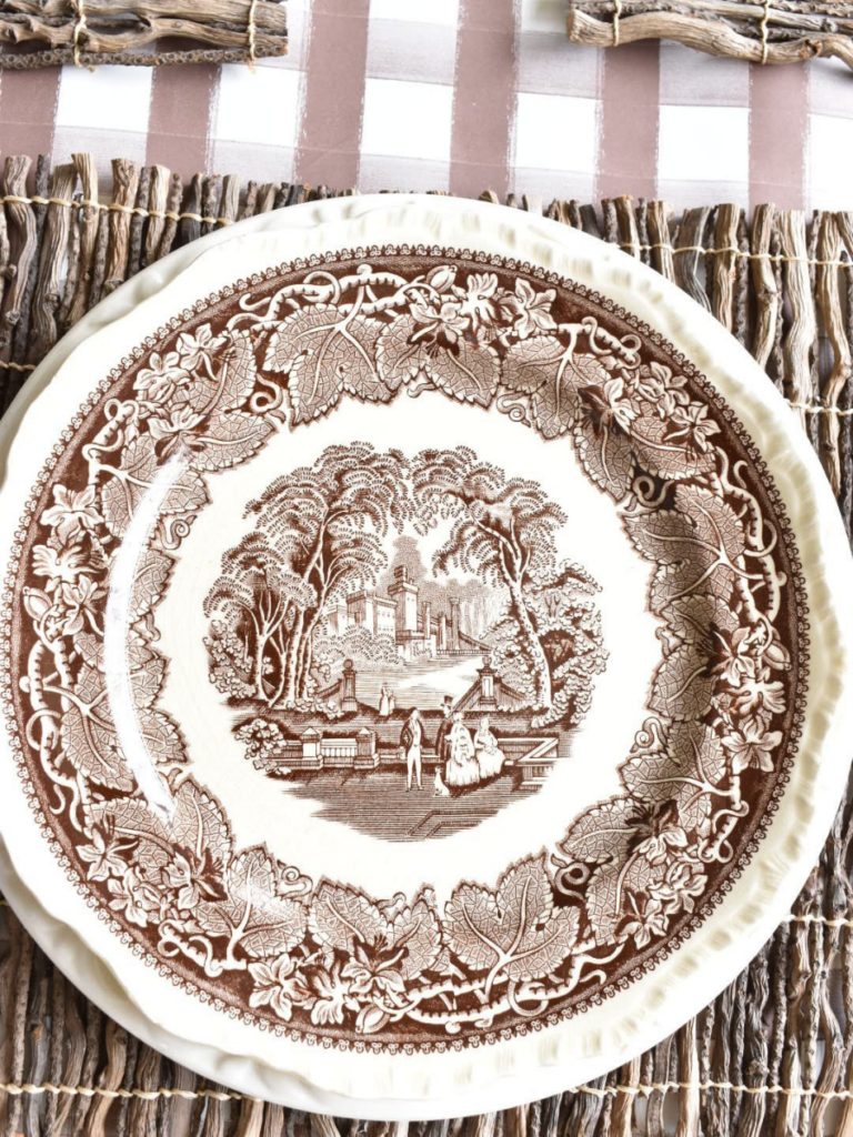twig placemat with a large white dinner plate layered with a smaller brown transferware dinner plate