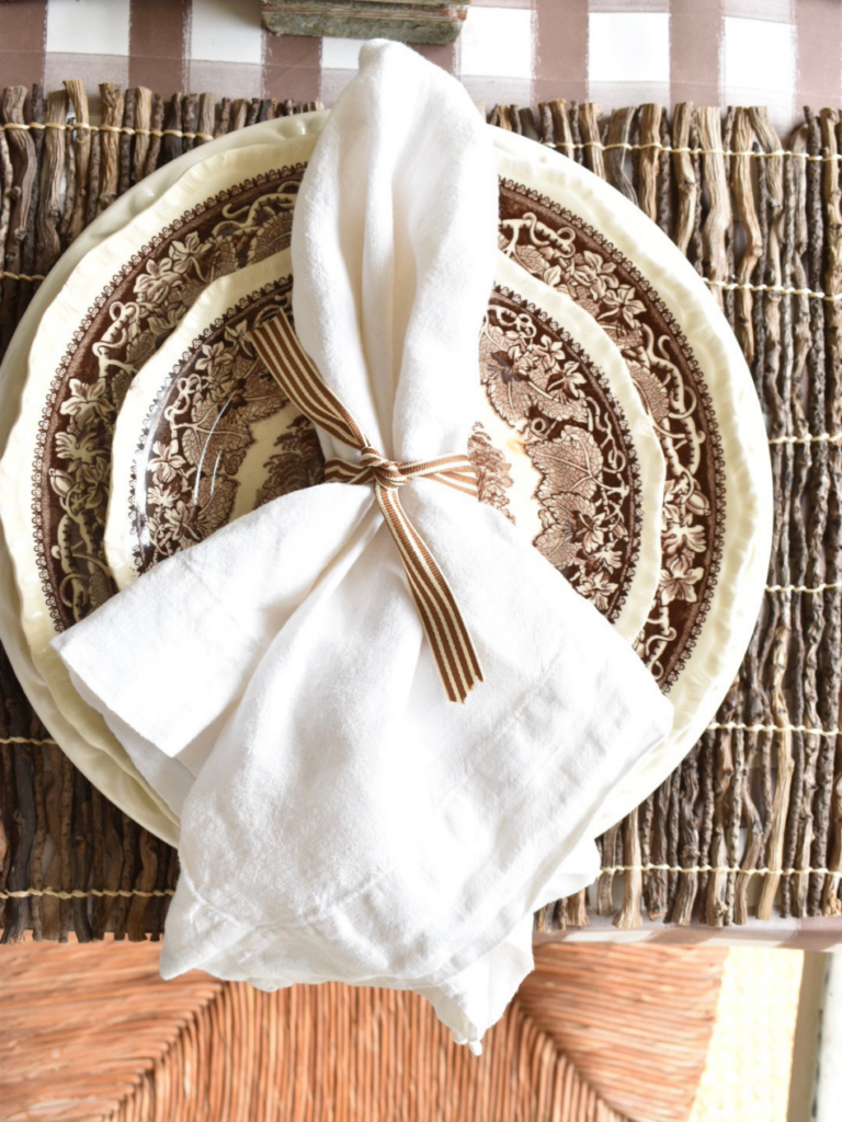twig placemat with a large white dinner plate layered with a smaller brown transferware dinner plate topped with a white linen napkin wrapped with brown striped ribbon