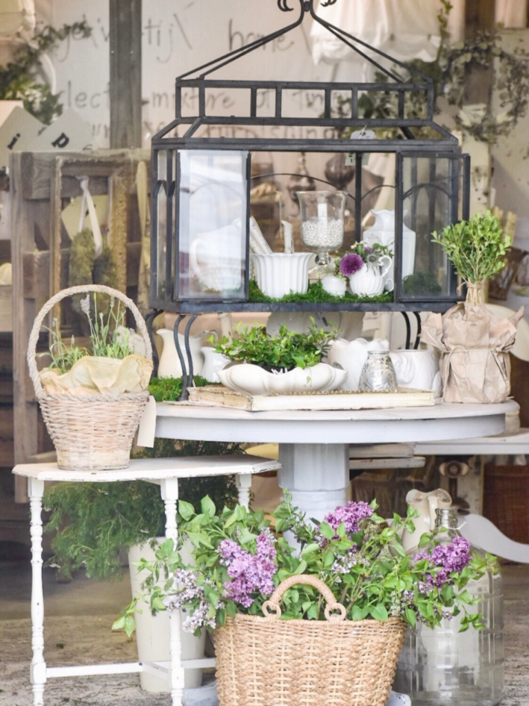 spring barn sale black and glass terrarium centerpiece on gray round table filled with plants and white ironstone pitches on table