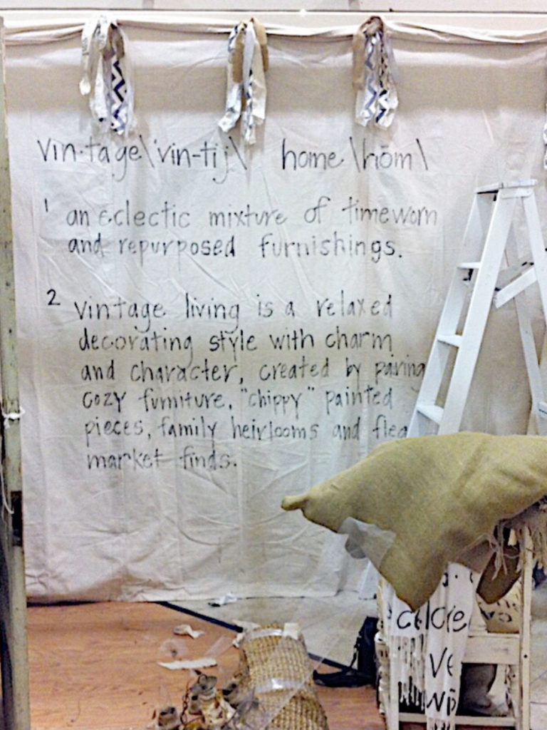 dropcloth backdrop in booth space with definition of vintage home written in gray words
