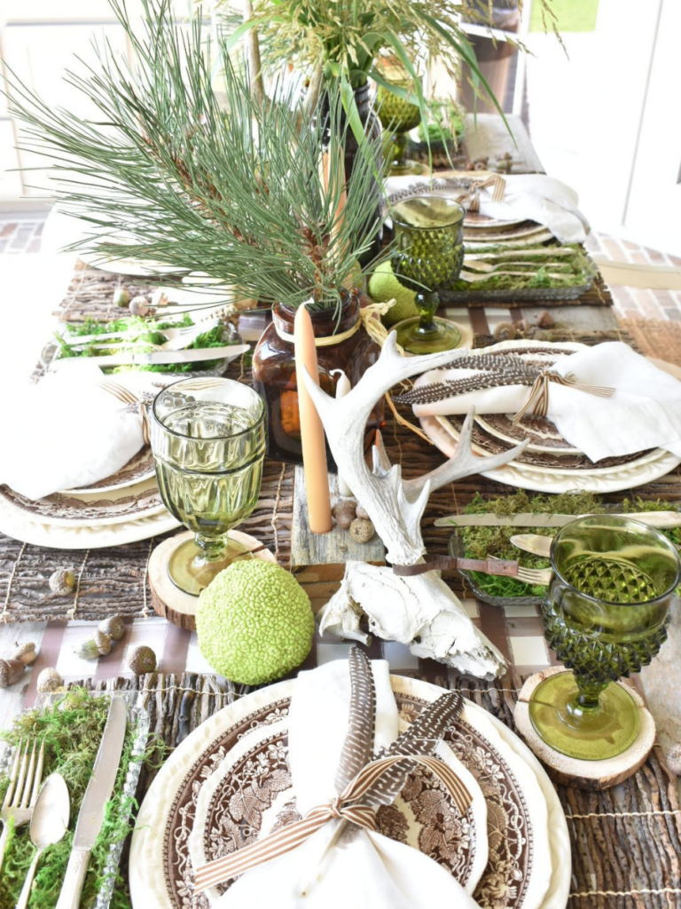 woodsy tablescape with brown paper plaid tablerunner twig placemat brown transferware dinner plate with brown transferware salad plate on top white linen napkin with 2 feathers on top silverware in a tray lined with green moss to the left of the place setting amber vases with pine branches for centerpiece amber bottles with tapers for centerpiece antlers acorns and horse apples for table