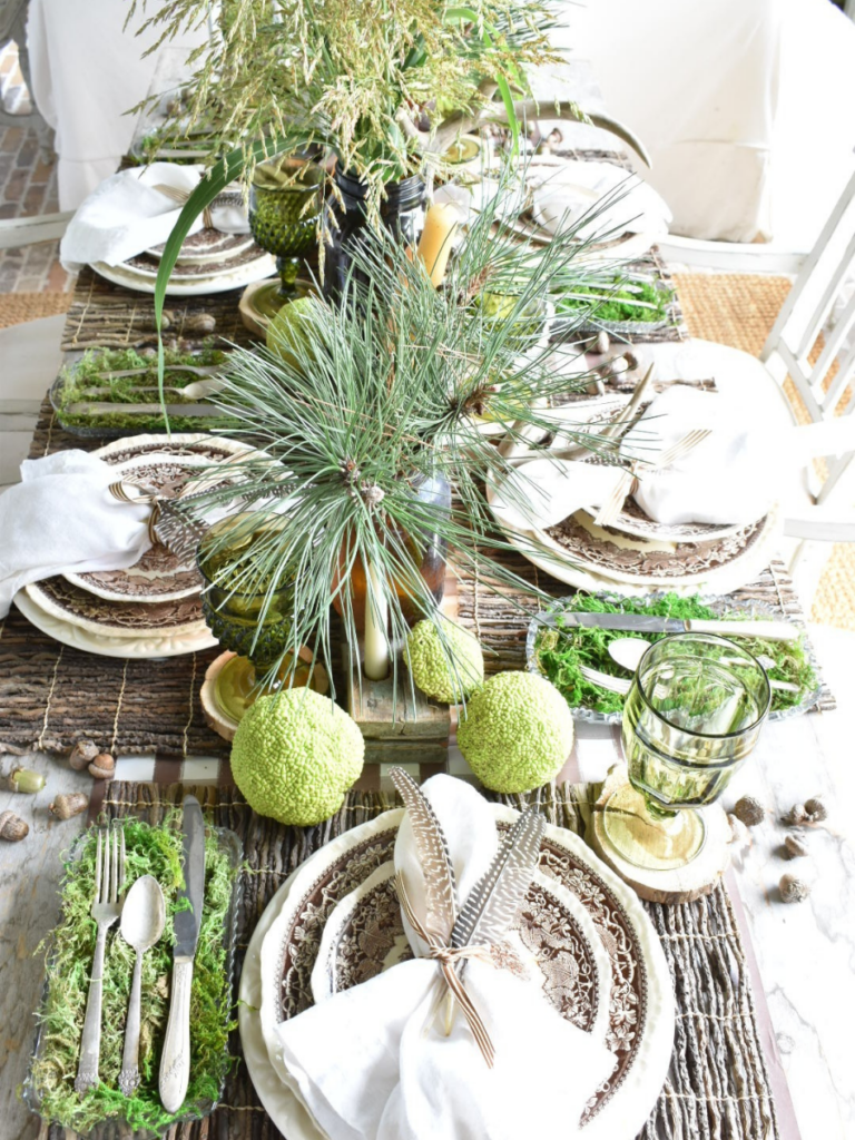 woodsy theme tablescape with brown paper plaid tablerunner twig placemat brown transferware dinner plate with brown transferware salad plate on top white linen napkin with 2 feathers on top silverware in a tray lined with green moss to the left of the place setting amber vases with pine branches for centerpiece amber bottles with tapers for centerpiece antlers acorns and horse apples for table