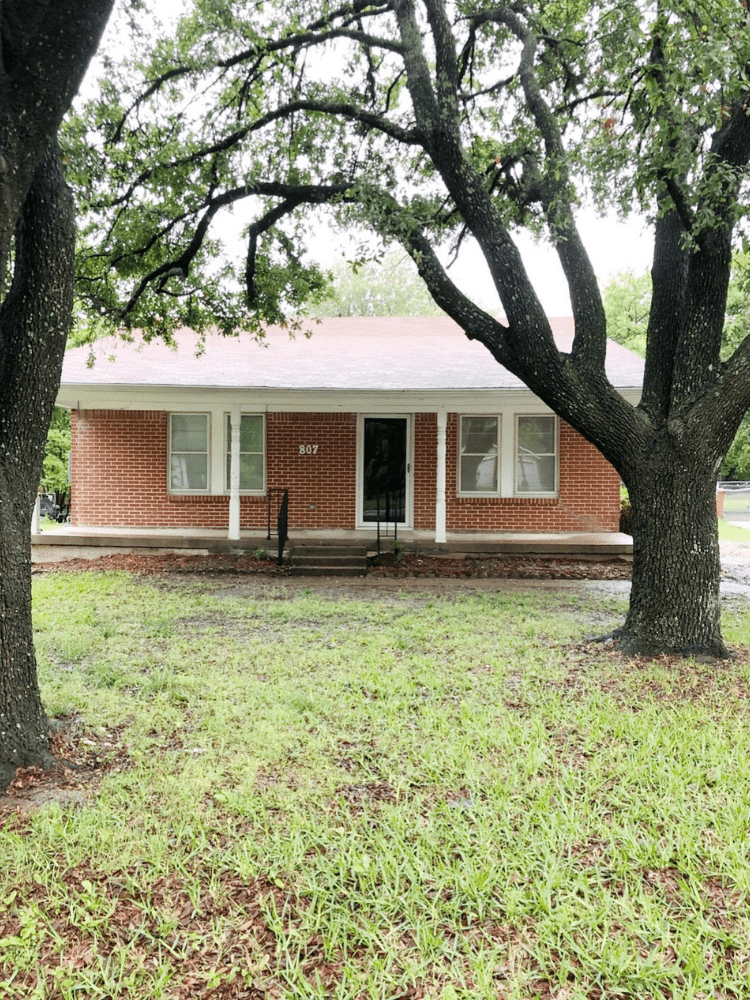 front view of a small red brick house with dark brown door and 2 large window on front