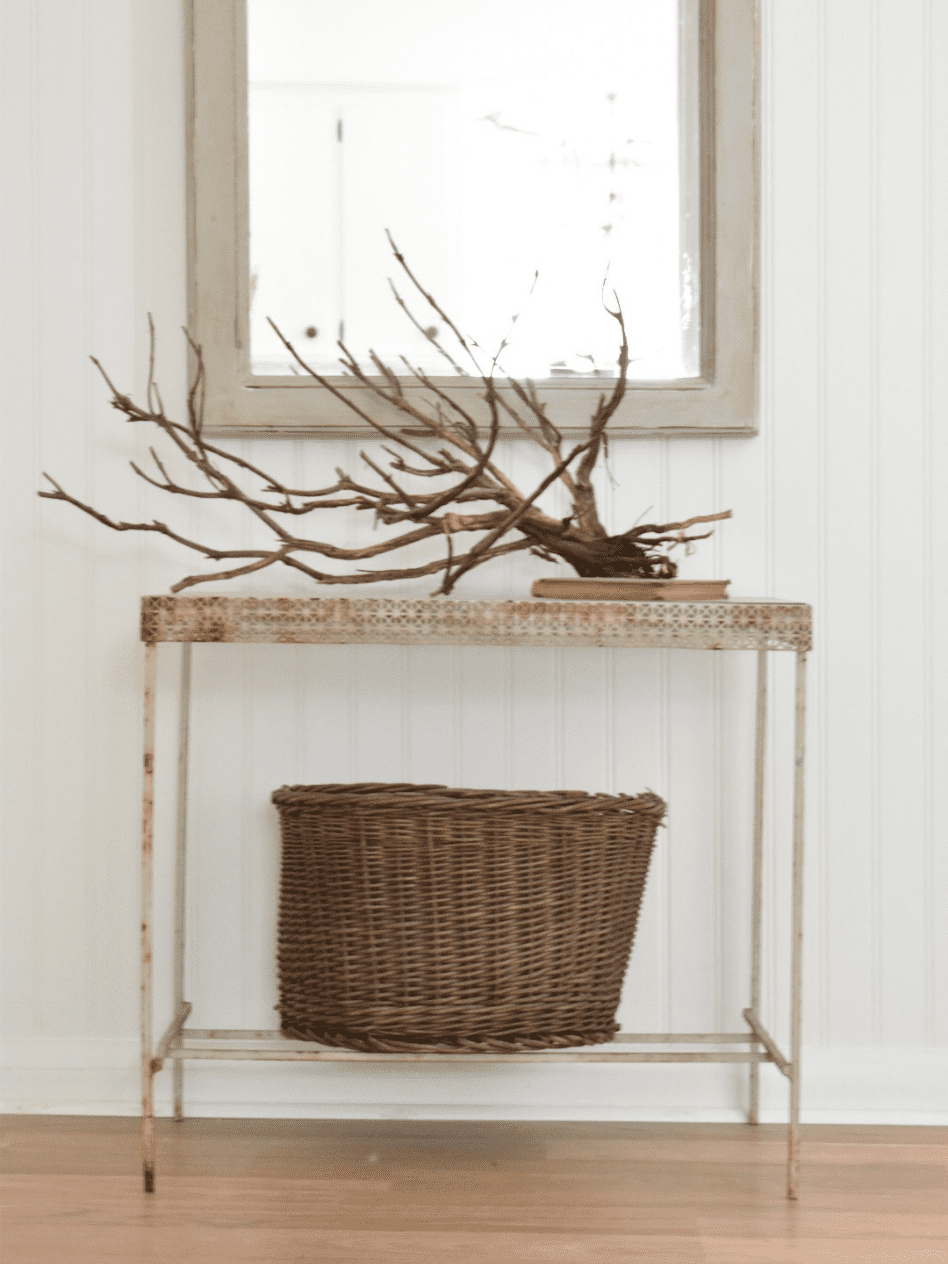 white metal table dead lavender branch vintage book on top of table basket on bottom shelf of table vintage mirror hanging above table