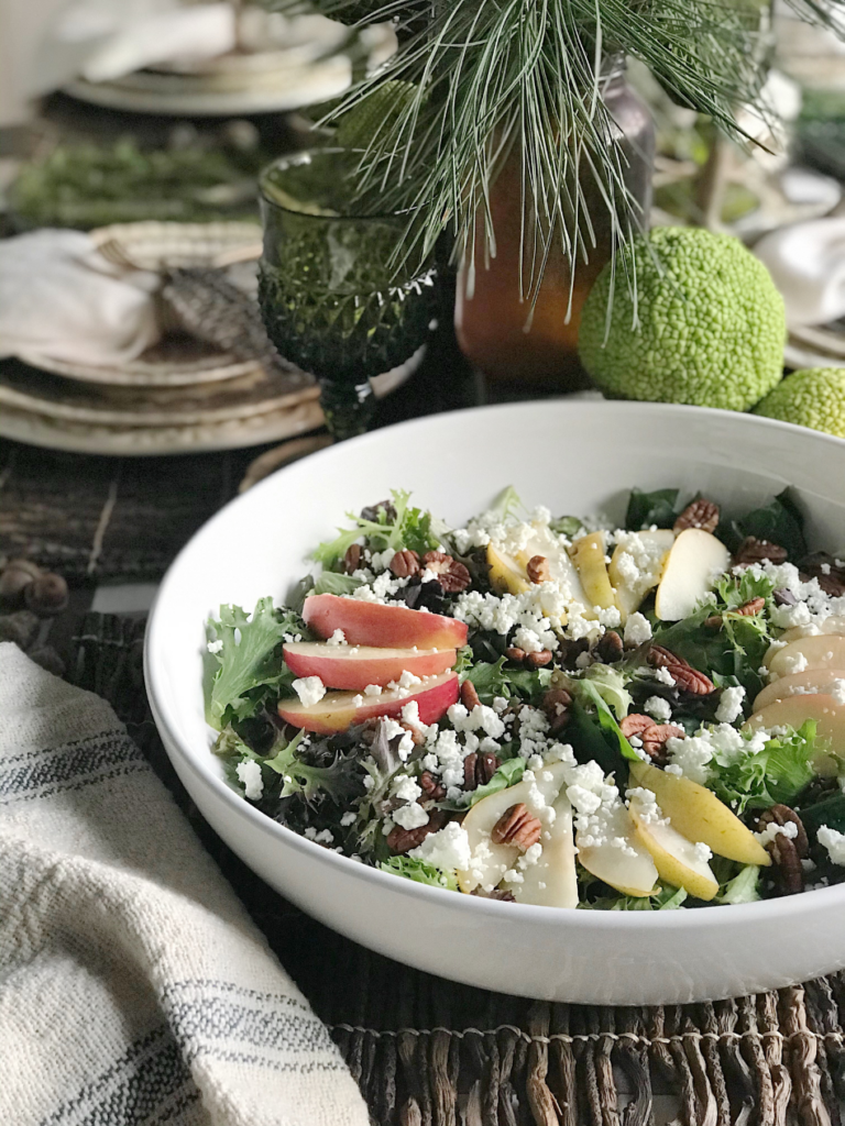 large white bowl with mixed greens pear slices apple slices pecan halves and goat cheese