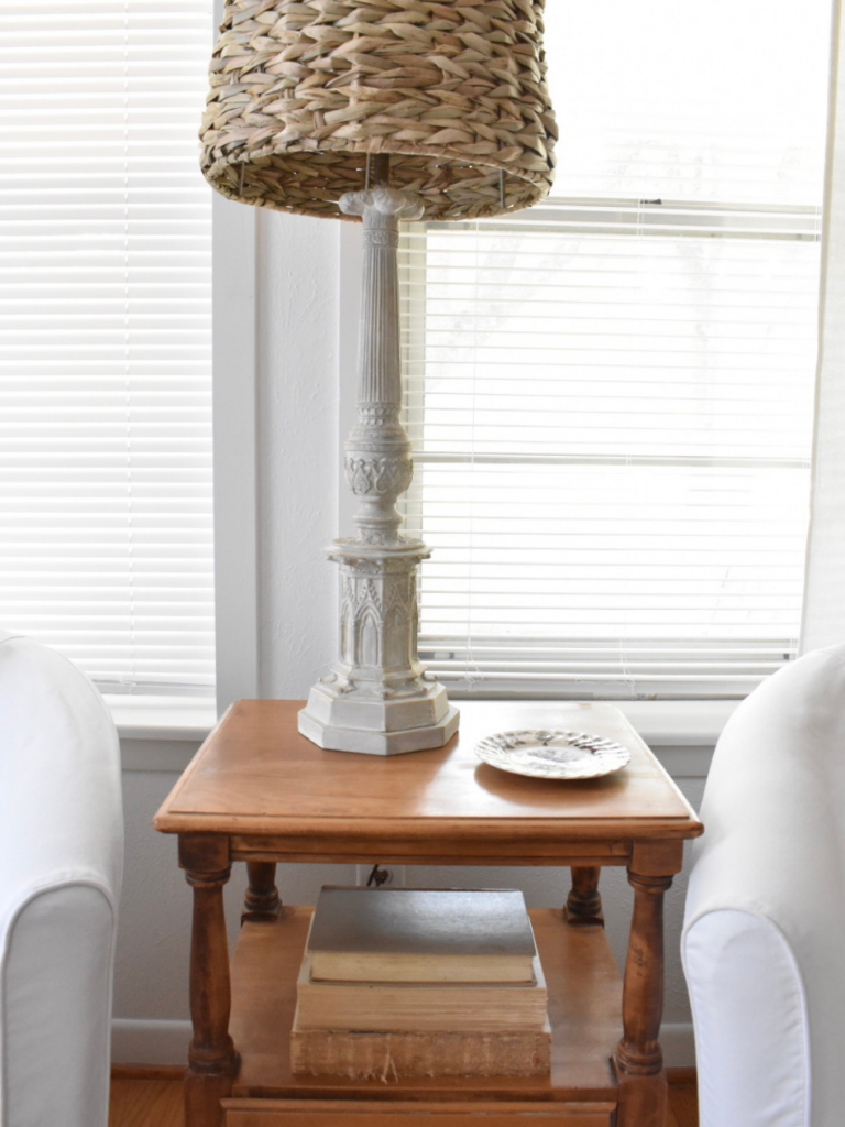 small wood side table with lamp and coaster beside white chair