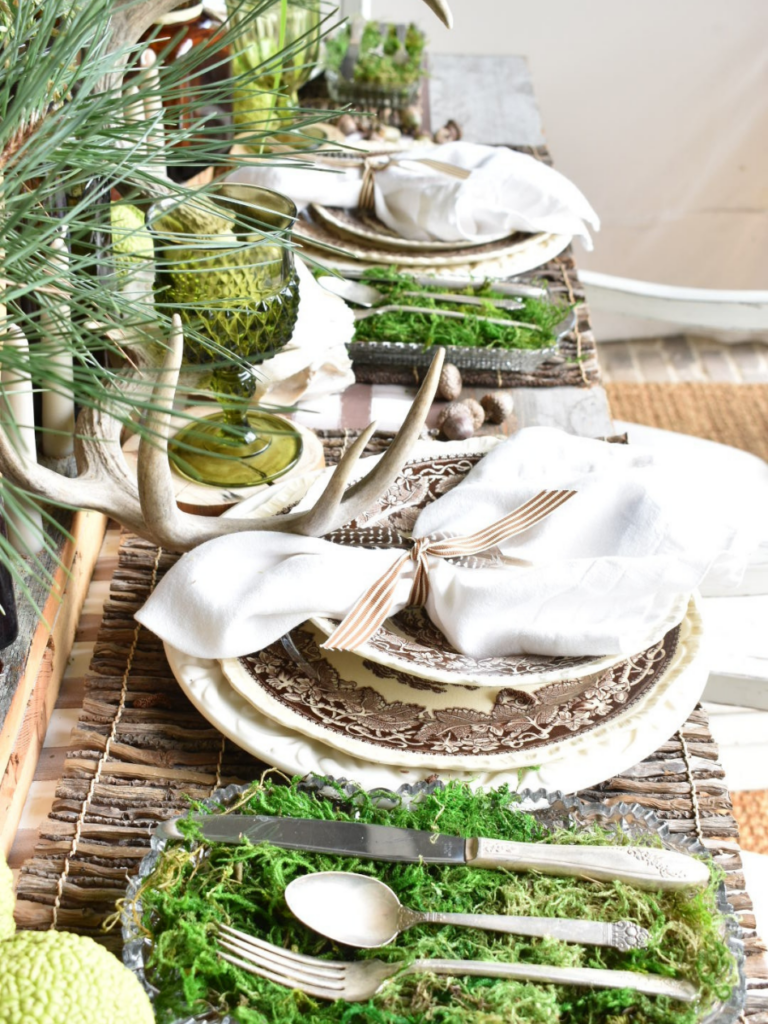 woodsy theme place setting with brown paper plaid tablerunner twig placemat brown transferware dinner plate with brown transferware salad plate on top white linen napkin with 2 feathers on top silverware in a tray lined with green moss to the left of the place setting amber vases with pine branches for centerpiece amber bottles with tapers for centerpiece antlers acorns and horse apples for table