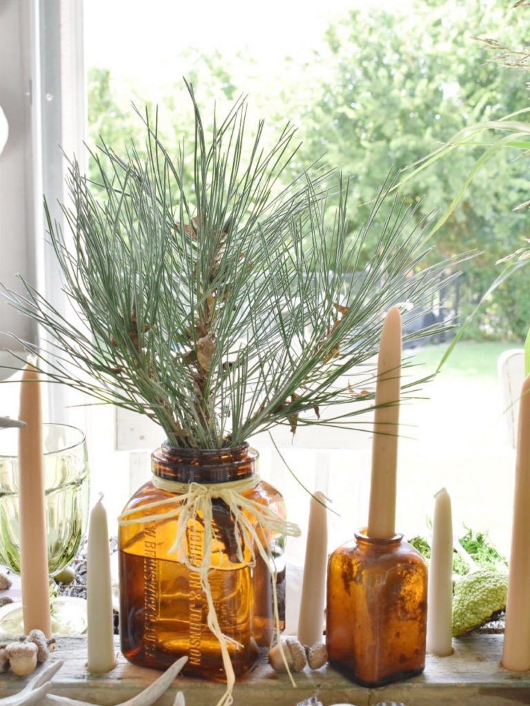 amber vase filled with pine branch and amber bottle with a taper sticking out for table centerpiece