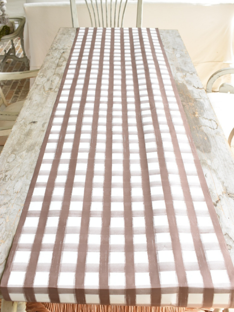 brown and white plaid paper table runner on outdoor rustic long dining table